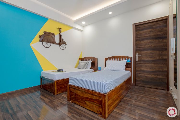 top interior designer kids room with two single beds and accent wall with scooter