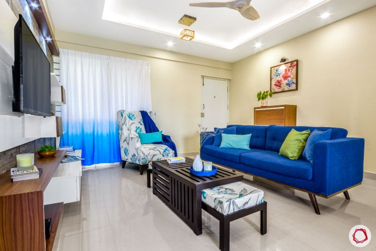 home bangalore-living room-seating area-blue sofa-cove lighting-printed accent chair