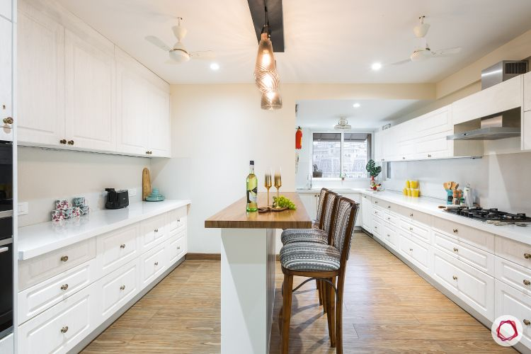 Vastu Colors for Kitchen-white-cabinets-handles-lights-chairs-breakfast-table